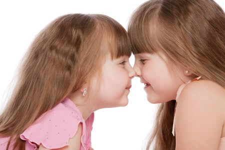 Two little sisters laughing, isolated Stock Photo - 4041385