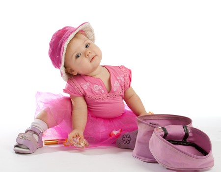 Little girl in pink sitting beside cosmetics box Stock Photo