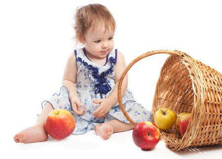 Toddler sitting near basket with fruit, isolated photo