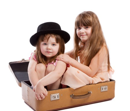 Two girls sitting in the old-styled shabby suitcase Stock Photo - 4162222