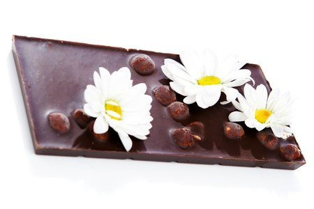 Dark chocolate bar with chamomile flowers on it photo