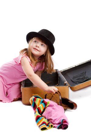 Girl packing old-styled shabby suitcase, isolated Stock Photo - 4173435