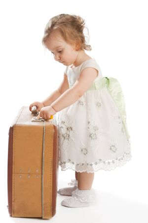 Toddler opens an old shabby suitcase Stock Photo - 4202422