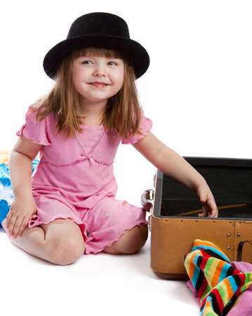 Laughing girl in hat sitting near open retro-styled suitcase Stock Photo - 4281636