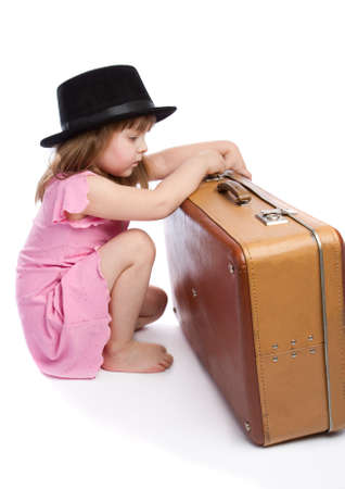Girl trying to open an old retro-styled suitcase Stock Photo - 4281571