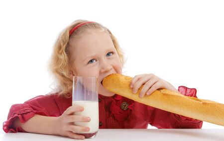 Girl sits at the table and bites a French bread Stock Photo - 4281576
