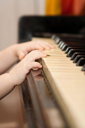 Young hands playing the old piano photo