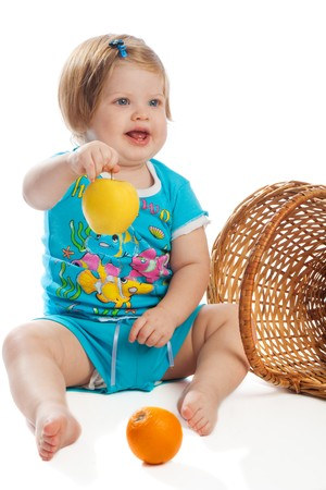 Child sitting near wicker basket and holding a yellow apple Stock Photo - 4332851