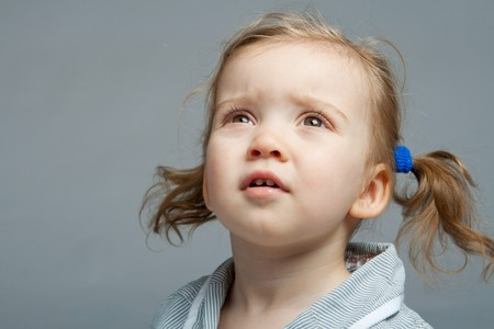 Portrait of a kid looking up, over grey background photo