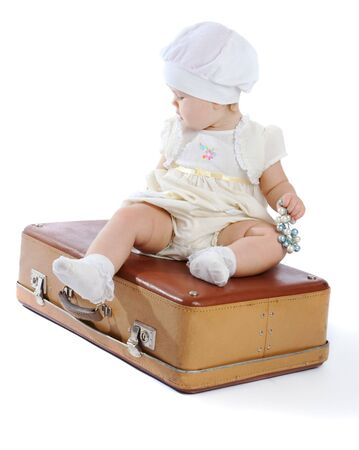 Toddler sitting on an old shabby suitcase Stock Photo - 4332815
