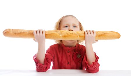 Cute blond girl sitting at the table and biting a French bread Stock Photo - 4332861