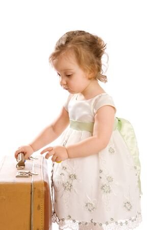 Toddler trying to open a retro-styled suitcase Stock Photo - 4355859