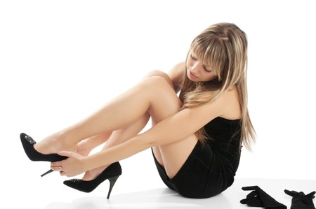 Girl in black evening dress putting on shoes photo