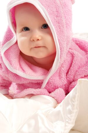Lovely baby in pink bath gown lying on satin blanket photo
