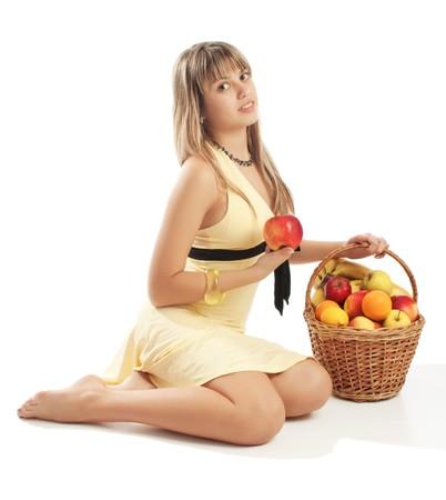 Girl in yellow dress sits near fruit basket photo