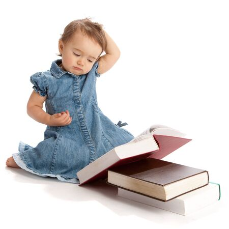 Little girl reading a book and scratching her head photo