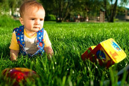 Baby on the lawn playing with toys photo