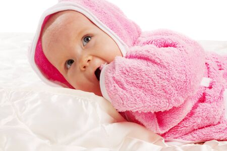 Baby lying on blanket in pink robe after bath  photo