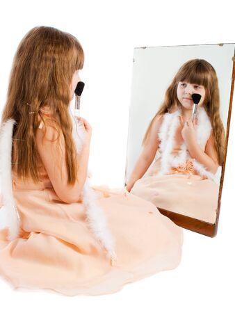Preschool girl sitting with brush in front of the mirror photo