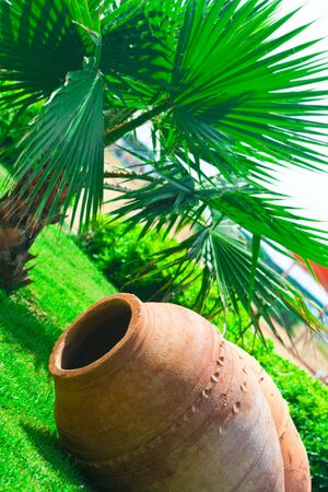 Large clay pitcher lying on grass photo