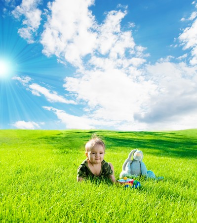 Charming baby sitting on green grass