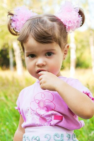 Little girl with finger in mouth, in the park photo