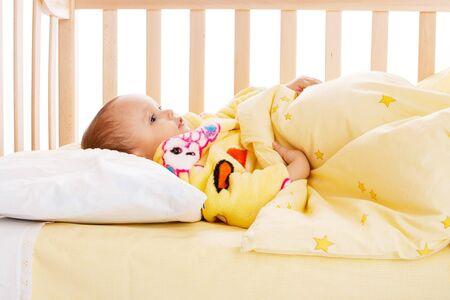 bath robe: Kid in yellow bath robe lying in the crib