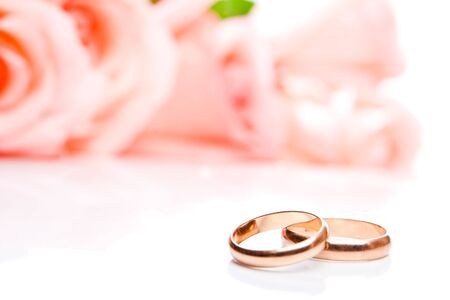 Wedding rings in front of roses, shallow focus on rings photo