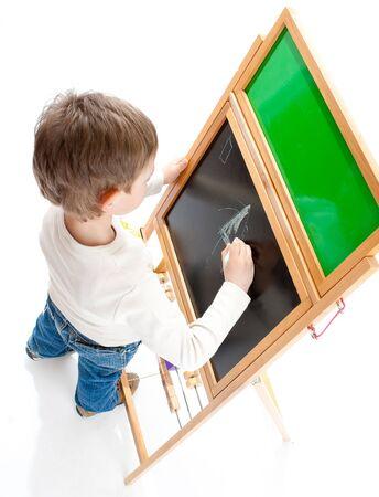 Preschool boy drawing on a blackboard, shot from top Stock Photo - 4710932