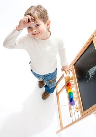 Smiling preschool boy near blackboard, shot from top photo