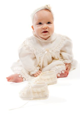 Baby in milky baptismal clothes sitting beside bootees photo