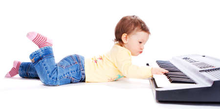 synthesizer: Baby lying on floor and playing synthesizer Stock Photo