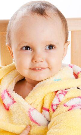 Baby portrait in yellow bath gown, sitting in a crib photo