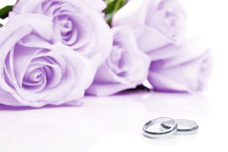 Two wedding rings made of white gold and purple roses in background
