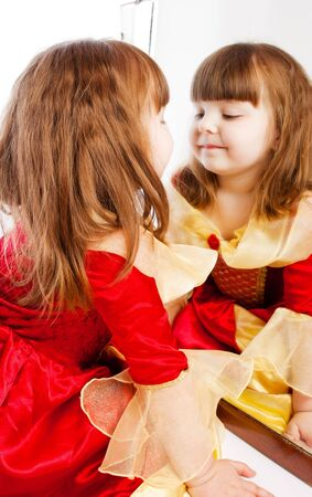 mirror face: Lovely preschool girl looking at her reflection in mirror Stock Photo