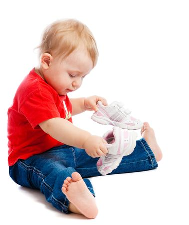Baby sitting on floor and trying on trainers Stock Photo - 4771268