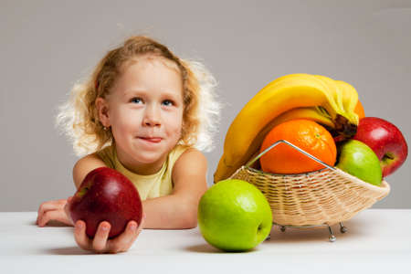 Girl licking her lips, sits at the table with fruit photo
