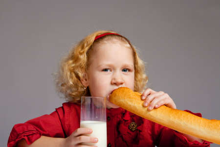 Lovely preschool girl biting French bread, on a gray background Stock Photo - 4827027