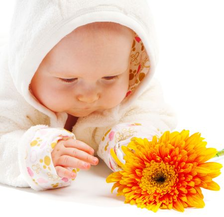 Baby lying on floor and looking at orange flower photo