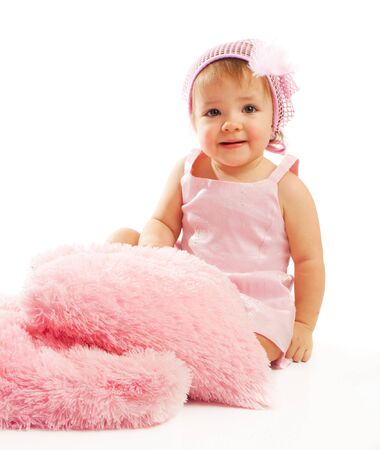 Baby girl sitting with pink fluffy pillows photo