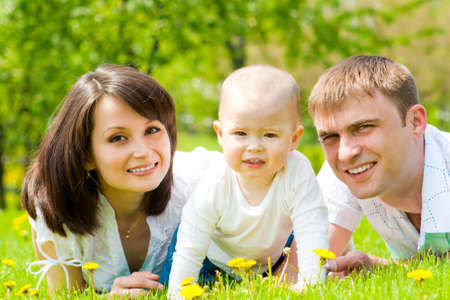 Happy family lying in summer park Stock Photo - 4845983