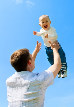 Father throwing baby boy against blue sky Stock Photo - 4846052