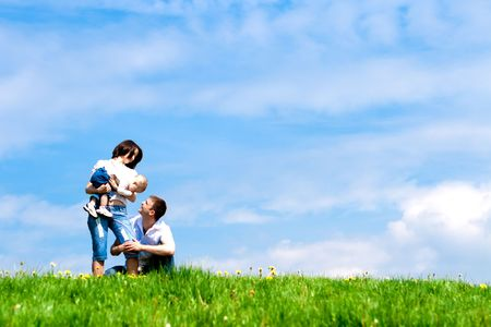 Happy mother, father and baby on the green hill