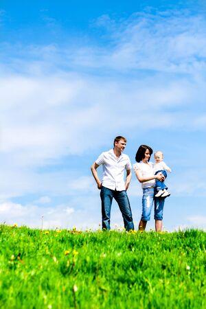 convivencia familiar: Joven familia feliz en la hierba verde sobre cielo azul profundo