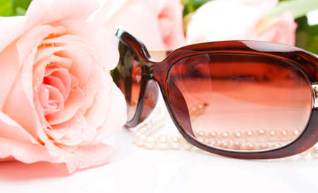 Pink rose, necklace and sunglasses, shallow focus photo