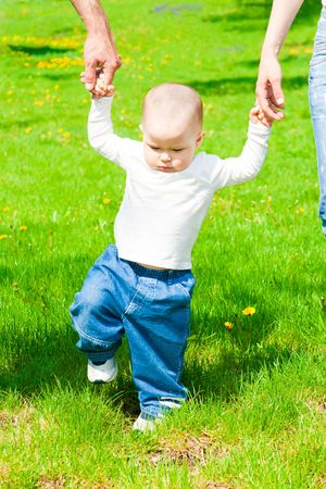 Baby walks in the park holding parents hands photo