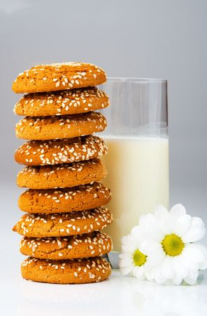 Biscuits in stack and milk glass, on grey photo