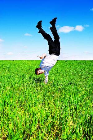Businessman upside down in the meadow photo