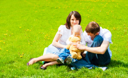 Attractive family playing on the meadow photo