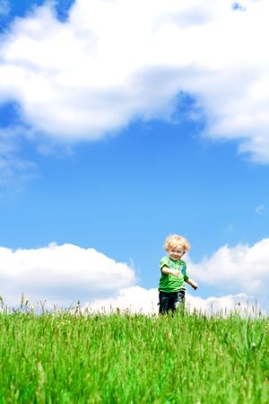 Blond curly toddler running in the grass photo